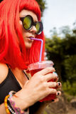 Woman with red hairs drink red cocktail. Stock Photo