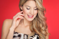 Woman On Red. Happy woman with beautiful long blond hair over red background Royalty Free Stock Photography