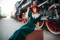 Woman in red hat against vintage steam train Royalty Free Stock Image