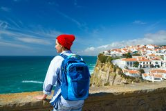 Woman with a backpack enjoys a view of the ocean coast near Azenhas do Mar, Portugal. Woman in red hat with a backpack enjoys a view of the ocean coast near stock photography