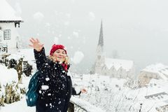 Woman in red hat playing snowballs in Hallstatt old town during snow storm, Austria. Woman in red hat having a snowball fight in Hallstatt old town during royalty free stock image