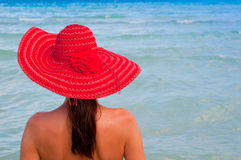 Woman with red hat looking at the sea. Beautiful woman with red hat looking at the summer sea Royalty Free Stock Images