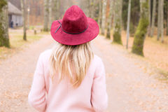 Woman in red hat and pink coat walking in park Stock Image
