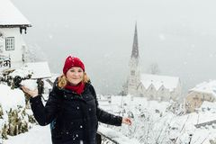 Woman in red hat playing snowballs in Hallstatt old town during snow storm, Austria. Woman in red hat having a snowball fight in Hallstatt old town during royalty free stock images