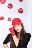 Woman with red hat between red balls Royalty Free Stock Photo