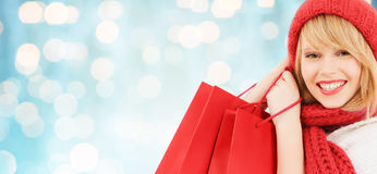 Woman in red hat and scarf with shopping bags Royalty Free Stock Photography