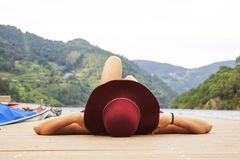 Woman sunbathing on pier. A woman with a red hat sunbathing on a wooden pier on a lake Royalty Free Stock Photo