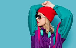 Woman in red hat, sunglasses and suit of 90s with headphones. Portrait of a woman in red hat, sunglasses and suit of 90s with headphones on blue background stock images