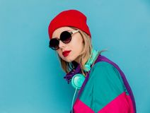 Woman in red hat, sunglasses and suit of 90s with headphones. Portrait of a woman in red hat, sunglasses and suit of 90s with headphones on blue background royalty free stock image