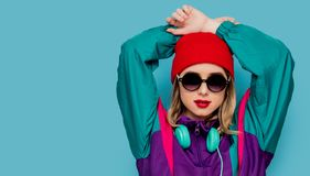 Woman in red hat, sunglasses and suit of 90s with headphones. Portrait of a woman in red hat, sunglasses and suit of 90s with headphones on blue background royalty free stock photos