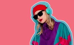 Woman in red hat, sunglasses and suit of 90s with headphones. Portrait of a woman in red hat, sunglasses and suit of 90s with headphones on blue and pink royalty free stock image