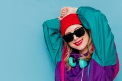 Woman in red hat, sunglasses and suit of 90s with headphones. Portrait of a woman in red hat, sunglasses and suit of 90s with headphones on blue background stock photos