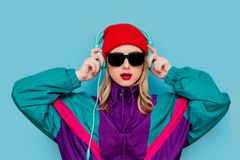 Woman in red hat, sunglasses and suit of 90s with headphones royalty free stock image