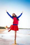 Woman in red have fun on the cost of lake Royalty Free Stock Photo