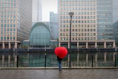 Woman with red, heart shaped umbrella stands in London Canary Wharf Royalty Free Stock Photos