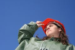 Woman with red helmet. Woman holding red safety helmet and with green plastic raincoat stock photo