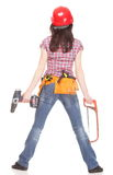 Woman in red helmet holding saw and drill Royalty Free Stock Photos