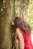 Woman in red hiding face. Woman in red with long wavy hair hiding face with arm leaning against a tree as if she were crying or if she were playing hide and seek Stock Images
