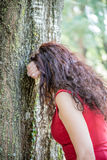 Woman in red hiding face. Woman in red with long wavy hair hiding face with arm leaning against a tree as if she were crying or if she were playing hide and seek Royalty Free Stock Photos