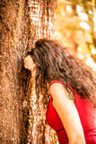 Woman in red hiding face. Woman in red with long wavy hair hiding face with arm leaning against a tree as if she were crying or if she were playing hide and seek Royalty Free Stock Image