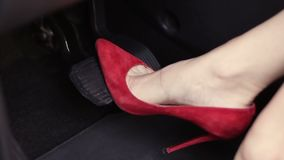 Woman in red high heels shoes pressing car pedals. Close-up slim female legs in red high heels shoes pressing the accelerator pedal of car and then elegant woman stock footage
