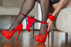Woman in red high heels shoes is pulling panties down Stock Photos