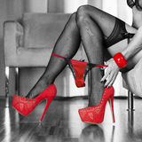 Woman in red high heels shoes is pulling panties down Stock Photo
