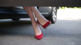 Woman in red high heels sitting in parked car stock footage