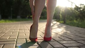 Woman in red high heels sprains foot on the street