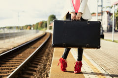 Woman in red high heels waiting in train station and holding suitcase Royalty Free Stock Photo