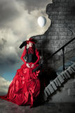 Woman in a red historic dress is standing on a background of a stormy sky. Woman in a red historic dress is standing on a background of a stormy sky near a Royalty Free Stock Image