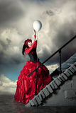 Woman in a red historical dress is catching a white balloon. Woman in a red historical dress is catching a white balloon against the backdrop of a stormy sky Royalty Free Stock Images