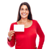 Woman in Red holding business Card. Young female Wearing red holding an empty Blank notecard isolated on White Royalty Free Stock Photography