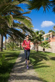 Woman running on wooden path between palm trees Royalty Free Stock Image