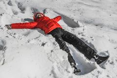 A woman in a red jacket and a black pants in a white snow in a winter park. A woman lies in snow like angel royalty free stock image