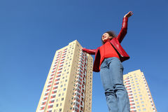 Woman in red jacket and blue jeans raises his hand stock photos