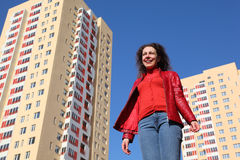 Woman in red jacket and blue jeans smiling Stock Images