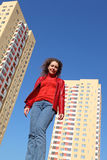 Woman in red jacket and blue jeans smiling Royalty Free Stock Image