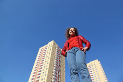 Woman in red jacket and blue jeans smiling Stock Photography