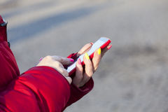 The woman in a red jacket dials number on phone Stock Photography