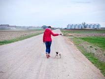 Woman with a red jacket go walkies with a pug on a gravel path. At countrye stock image