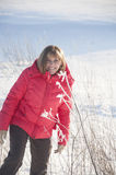 The woman in the red jacket. Goes through a field of snow royalty free stock images