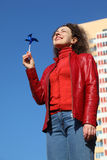 Woman in red jacket and jeans playing with spinner Stock Images