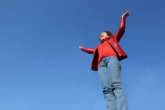 Woman in red jacket and jeans raises his hand Stock Image