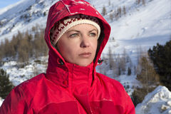 Woman with red jacket looks into the distance in the mountains Stock Photos