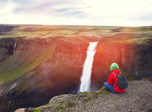 Woman in red jacket relax on cliff near fantastic waterfall Stock Images