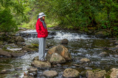 Woman in red jacket by the river stock photos