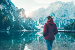 Woman in red jacket standing on the coast of Braies lake stock image