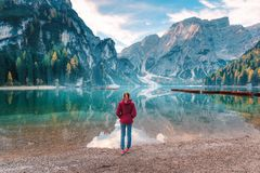 Woman in red jacket standing on the coast of Braies lake stock photos