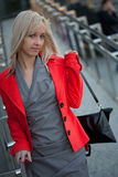 Woman in red jacket standing on the shop Stock Images